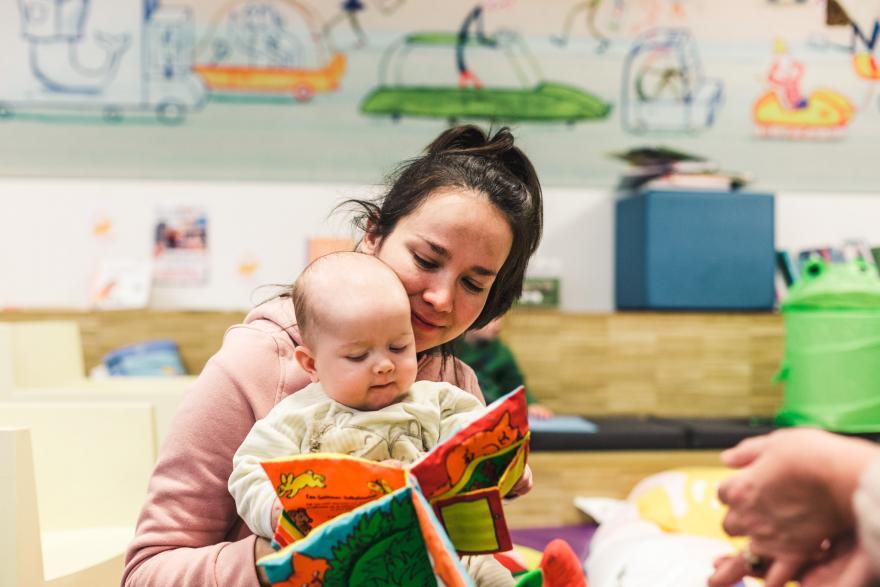 mama kijkt met baby in boek