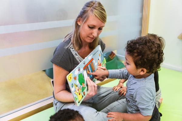 kinderbegeleidster leest voor aan peuter.